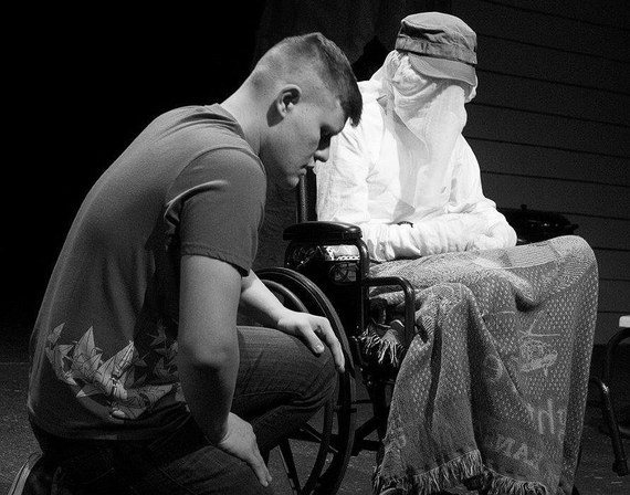 A young man kneels, head bowed, next to a veiled woman in a wheelchair