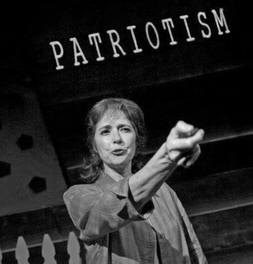 A woman stands with a beamer in her outstretched hand in front of a screen which reads Patriotism in large letters