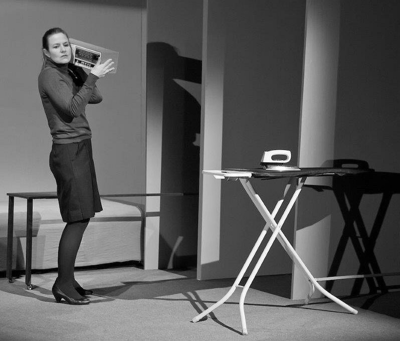 A woman stands transfixed next to her ironing board with a radio against her ear