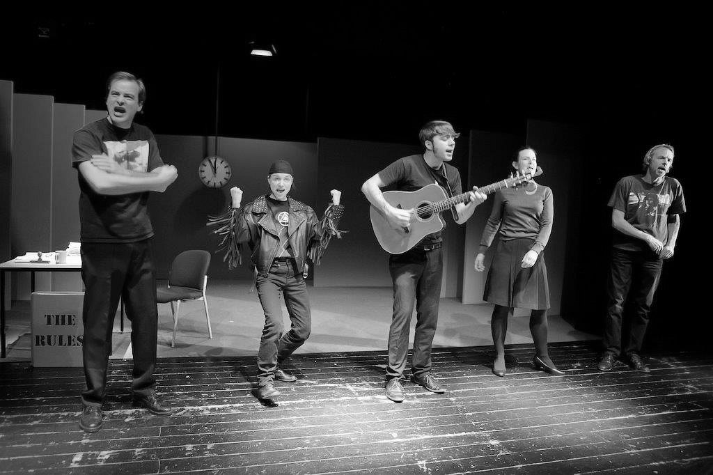 Five characters stand downstage singing a song out to the audience, the middle actor plays a guitar
