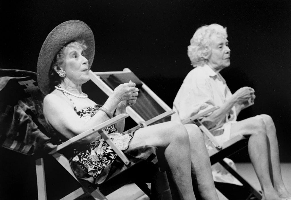 Two elderly women in bathing suits sit on beach chairs looking out into the sea