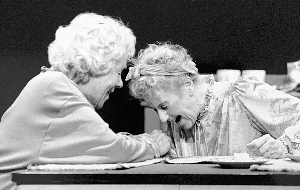 Two elderly women sit holding hands and laughing together at a table