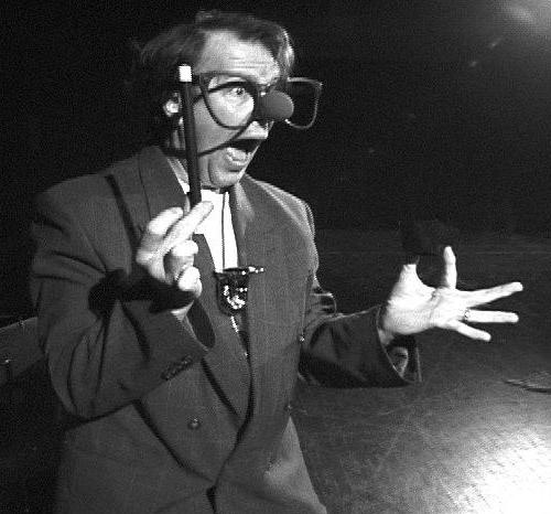 A man in a suit with a clown nose, over-sized glasses and a pointer performs open-mouthed surprise for an audience